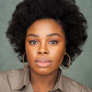 A person looking into the camera with afro texture hair wearing gold hoops against a grey green background