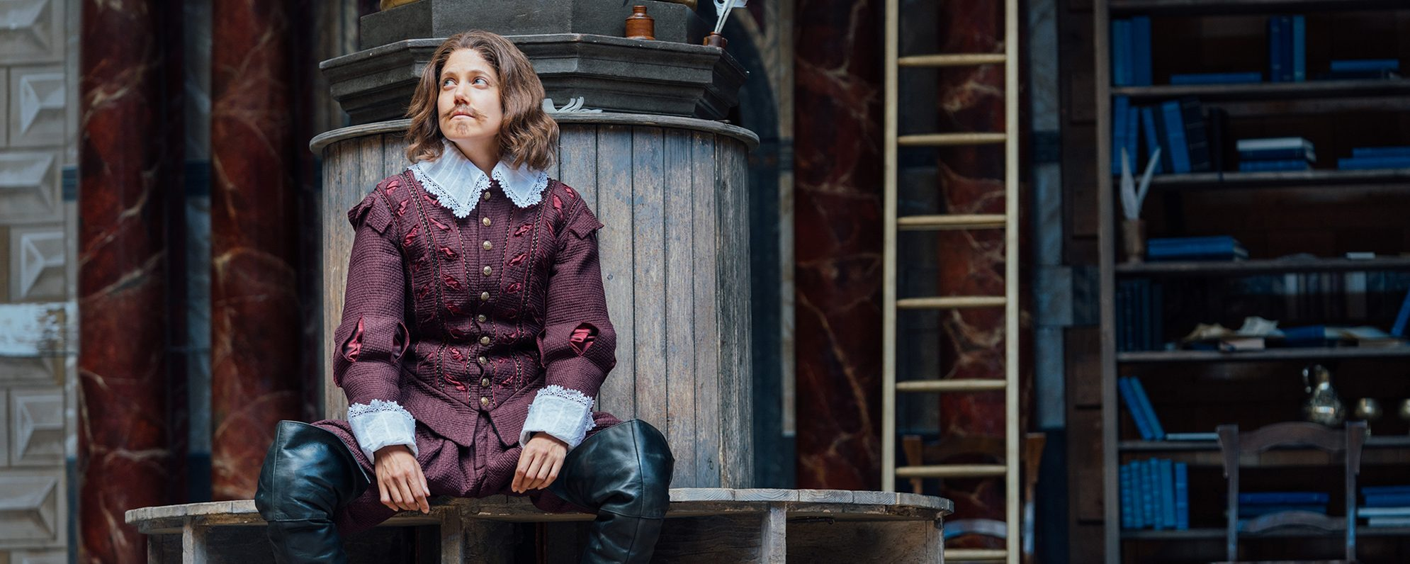 An actor playing William Shakespeare sits by a pillar on the Globe stage