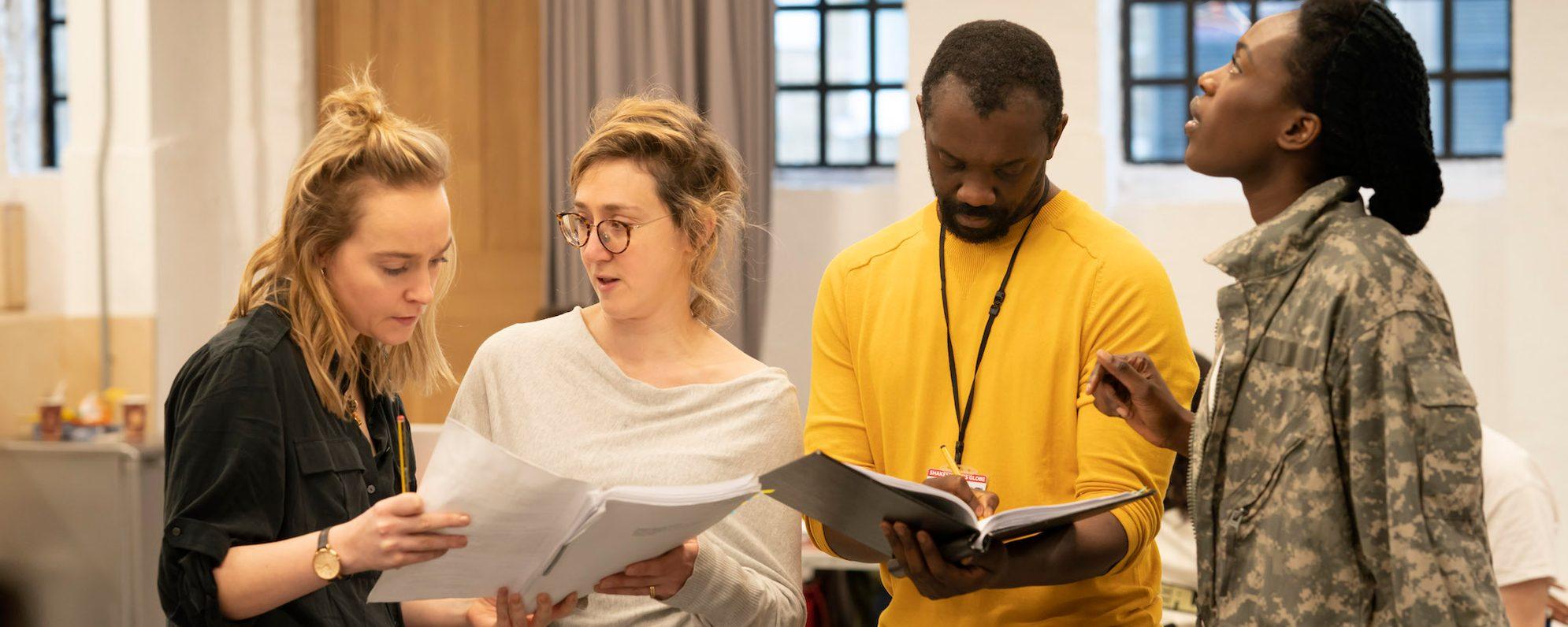 A group of four actors in rehearsal together look at their scripts