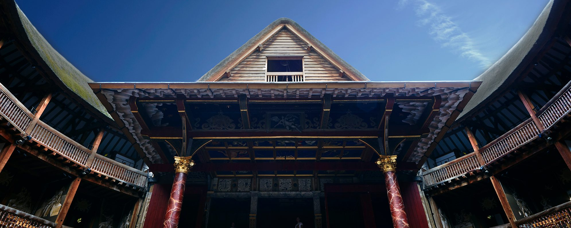 A blue sky over the pointed roof of a timber structure theatre.