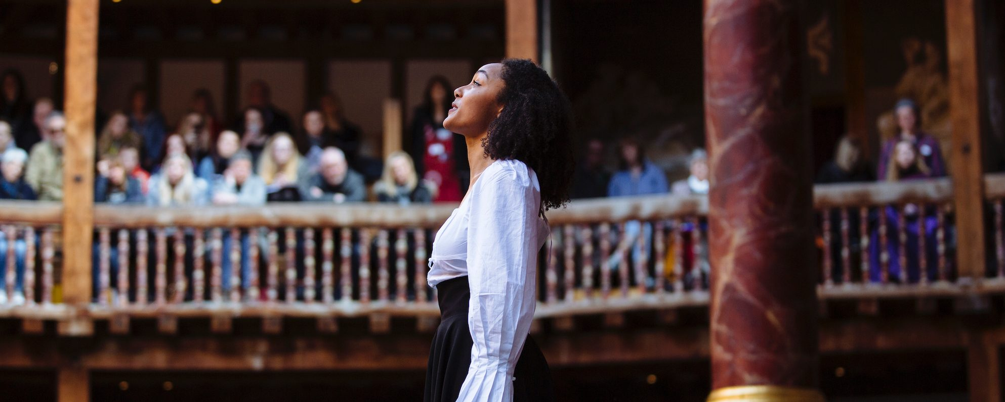 An actress stands on stage looking up to the sky