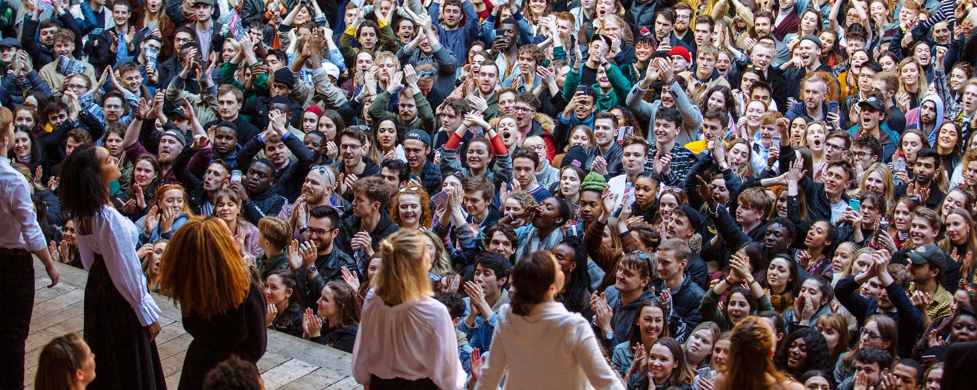 A large group of people stand and watch an outside performance