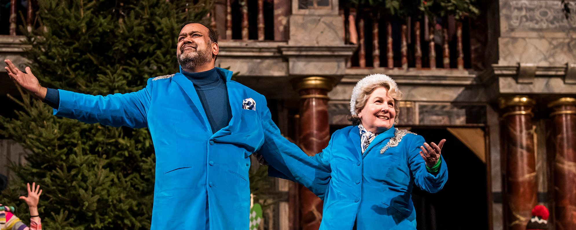 A male and female actor, wearing matching blue suits, stand onstage with their arms outstretched, smiling.