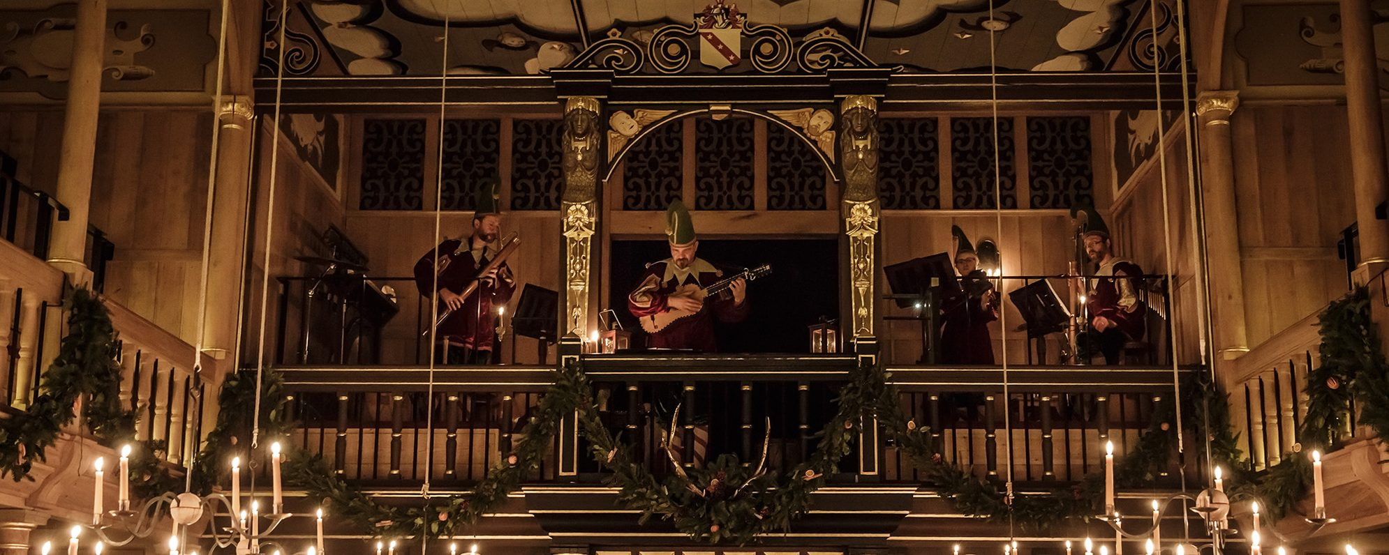 A group of musicians play lutes and pipes in the gallery of a candlelit theatre.