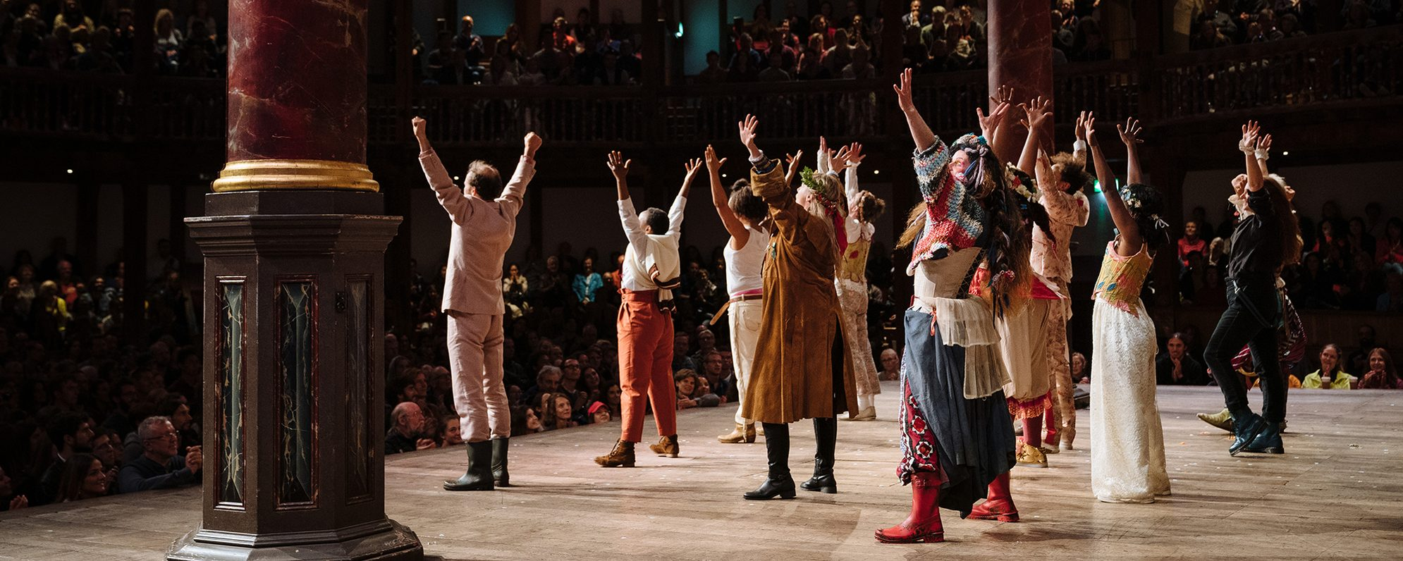A group of actors stand on the Globe Theatre stage, their arms raised in the air, looking out at the audience.