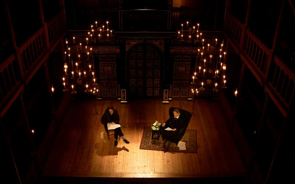 Two actors sit on the stage of the Sam Wanamaker Playhouse with fairy lights above them