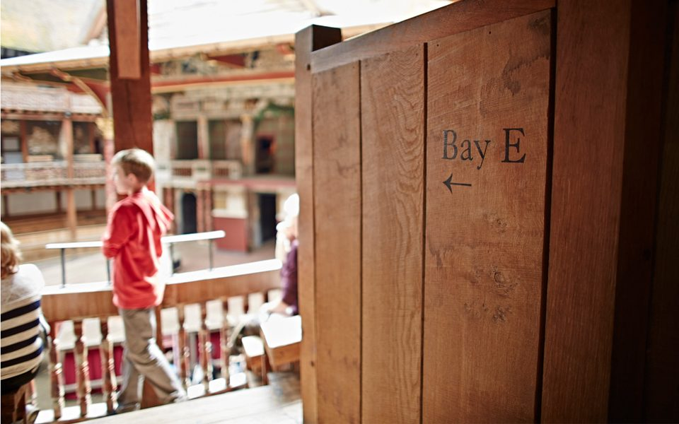 A photo taken from the side of Bay E in the Globe theatre, while a child looks out during a tour