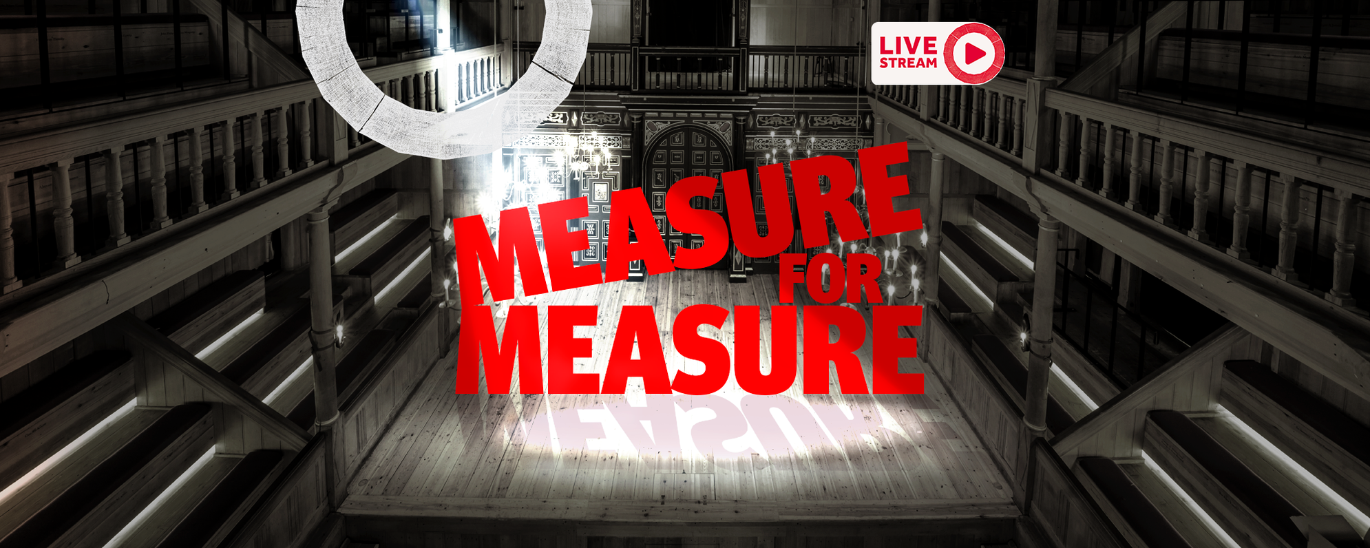 A black and white photograph of the stage in the Sam Wanamaker Playhouse. It is ornate and wood-panelled. In the centre of the stage are the words Measure for Measure in bright red, block writing. A spotlight is shining on the words, casting a shadow the stage.