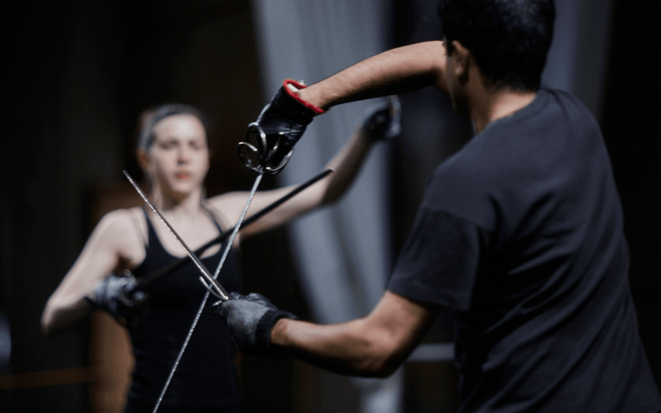Two people hold swords in a sword fighting demonstration.