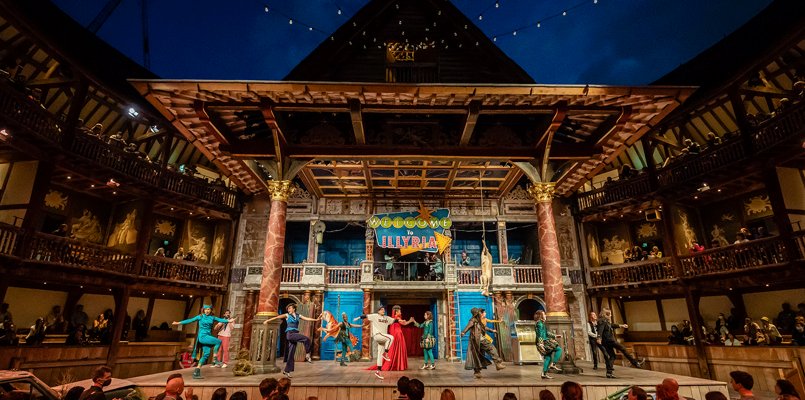 A dark cloudy night sky above the Globe Theatre stage: with fairy light hanging across the open-air roof.